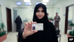 This image released by the Saudi Information Ministry shows Tahani Aldosemani, assistant professor at Prince Sattam Bin Abdulaziz University in Al-Kharj, as she displays her new driving license at the General Department of Traffic in the capital, Riyadh, June 4, 2018.