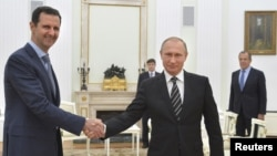 ປະທານາທິບໍດີ ຣັດເຊຍ ທ່ານ Vladimir Putin (ຂວາ) ສຳພັດມືກັບ ປະທານາທິບໍດີ Bashar al-Assad ລະຫວ່າງການ ພົບປະກັນທີ່ ວັງ Kremlin ທີ່ Moscow, ຣັດເຊຍ.