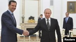 ປະທານາທິບໍດີຣັດເຊຍ ທ່ານ Vladimir Putin (ຂວາ) ຈັບມືກັບ ປະທານາທິບໍດີຊີເຣຍ ທ່ານ Bashar al-Assad ລະຫວ່າງ ກອງປະຊຸມ ທີ່ວັງ Kremlin ໃນນະຄອນມົສກູ.