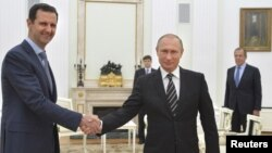 Russian President Vladimir Putin (R) shakes hands with Syrian President Bashar al-Assad during a meeting at the Kremlin in Moscow, Russia, Oct. 20, 2015.