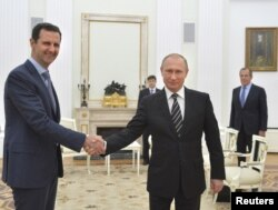 Russian President Vladimir Putin, right, shakes hands with Syrian President Bashar al-Assad during a meeting at the Kremlin in Moscow, Russia, Oct. 20, 2015.