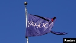 A flag bearing the Yahoo company logo flies above a building in New York, Oct. 31, 2016. The European Commission has asked the U.S. about a secret court order Yahoo used to scan thousands of customer emails.