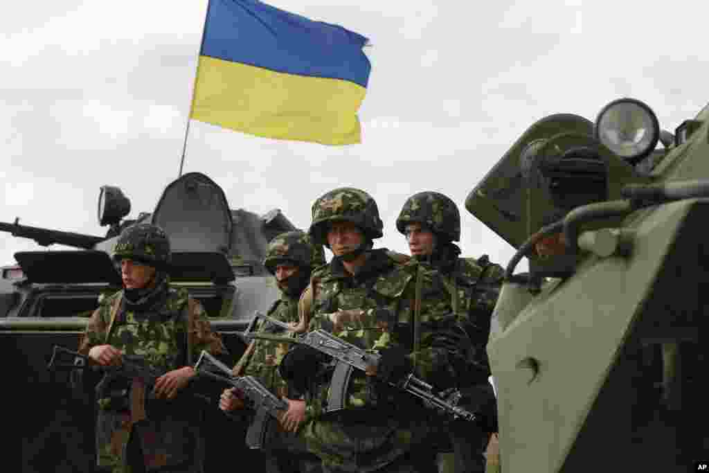 Ukrainian soldiers stand near APCs, that fly a Ukrainian flag, as army troops receive ammunition in a field on the outskirts of Izyum, April 15, 2014.