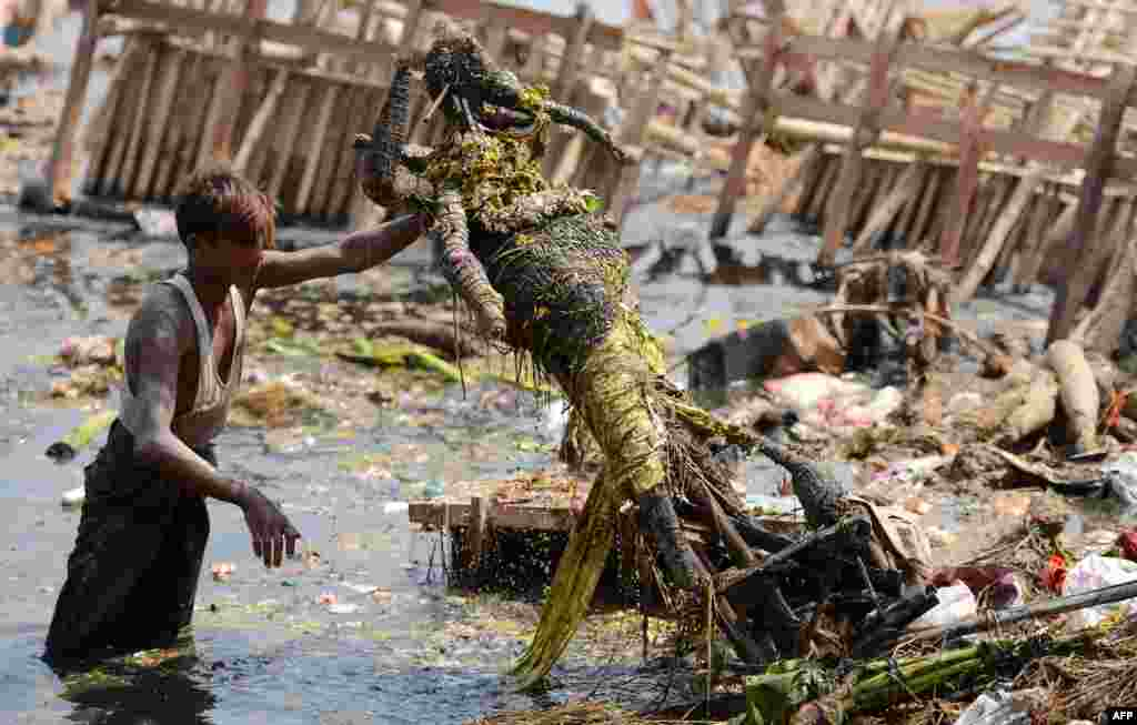 Workers remove religious offerings and frames of the idol of goddess Durga which were immersed in the Yamuna river after the Durga Puja festival in New Delhi, India.