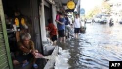 Một người đàn ông đang tát nước tràn vào nhà trong khi mực nước sông Chao Phraya dâng cao tràn lên đường phố trong quận Phranakhon của Bangkok hôm 24/10/11