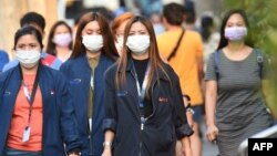 Office employees wearing facemasks walk along a street in Manila on January 30, 2020.