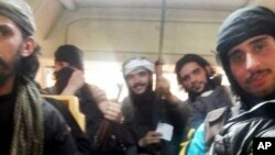This May 7, 2014 photo provided by the anti-government activist group Coordination Committee of Khalidiya Neighborhood in Homs, which has been authenticated based on its contents and other AP reporting, shows Free Syrian Army fighters on a bus