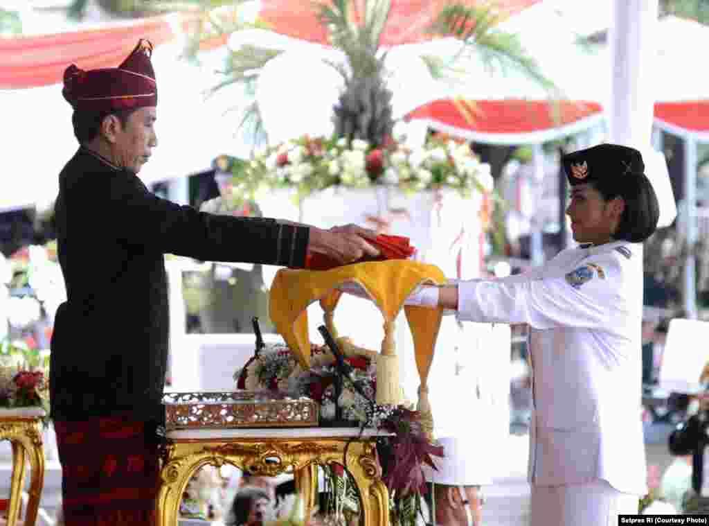 Presiden menyerahkan bendera merah putih kepada Fariza Putri Salsabila yang mewakili Provinsi Jawa Timur untuk kemudian dikibarkan, Jakarta, 17 Agustus 2017. (Courtesy: Setpres RI)