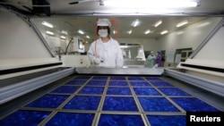 中国浙江省嘉兴的太阳能板工厂工人在把新制成的太阳能板作干燥处理。