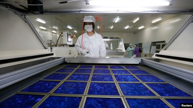 An employee dries newly made solar panels at a factory of a photovoltaic company in Jiaxing, Zhejiang province, June 5, 2013.