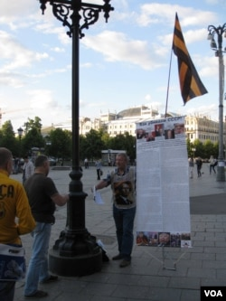 这位普京支持者反对苏联解体。他打着乌克兰东部亲俄势力的旗帜在莫斯科市中心向行人介绍戈尔巴乔夫和叶利钦等人的行动如何导致苏联灭亡。2014年8月。(美国之音白桦拍摄)