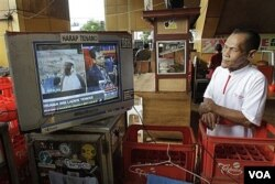 Seorang warga Jakarta menonton siaran televisi yang memberitakan tewasnya Osama bin Laden, Senin (2/5).