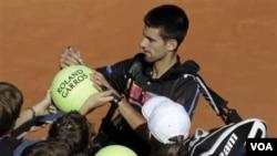 Novak Djokovic memberikan tanda tangan kepada penggemarnya setelah petenis Romania Victor Hanescu mengundurkan diri dari putaran kedua Perancis Terbuka hari Rabu (25/5).