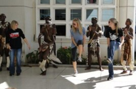 Study abroad students (from left) Gina Nuccio, Hillary Kinsey and Alyssa Crosby dance with Zulu musicians and performers wearing traditional tribal clothing.