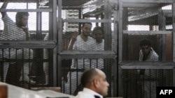 Bị cáo bị giam trong lồng trong phiên tòa xét xử 20 người, trong đó có 5 phóng viên của đài al-Jazeera,ngày 3 tháng 5, 2014.