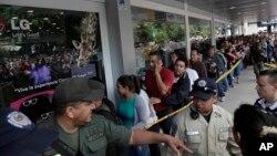 Largas filas se forman al frente de los supermercados para conseguir los productos básicos.