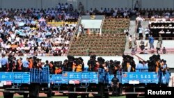 Trucks carrying criminals and suspects are seen during a mass sentencing rally at a stadium in Yili, Xinjiang, Uighur Autonomous Region, May 27, 2014.