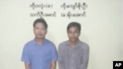 In this image released by the Myanmar Ministry of Information and broadcast by Myanmar's MRTV, on Dec. 13, 2017, Reuters reporters Wa Lone, left, and Kyaw Soe Oo stand handcuffed in Myanmar.