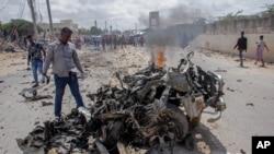 Pripadnici snaga bezbjednosti i civili u blizini olupine nakon napada automobilom-bombom na gradskok policijskog komesara u Mogadišu, Somalija, 10. jula 2021.