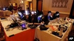 Piratas cibernéticos participan en una competencia en la conferencia DefCon, en esta foto de archivo del viernes 5 de agosto de 2011 en Las Vegas. La semana pasada dos niños de 11 años que participaron en una conferencia similar lograron hackear una réplica del sitio web de elecciones de La Florida.