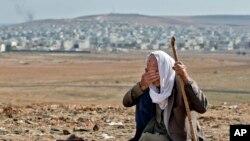 Pengungsi Kurdi Suriah, Mohammad Hassan, 84 tahun, dari Kobani menangis, dengan latar belakang kampung halamannya, di bukit pinggiran Suruc, Turki, dekat perbatasan Turki-Suriah, Minggu, 26 Oktober 2014.