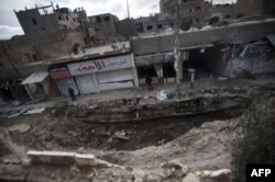 FILE - A massive bomb allegedly dropped by pro-government war planes levels part of the eastern Syrian city of Deir Ezzor, Feb. 16, 2013