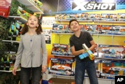 A brother and sister check out the latest gadgets at the International Toy Fair, in New York, Feb. 17, 2018.