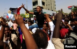 Sudanese demonstrators protest against the army's announcement that President Omar al-Bashir would be replaced by a military-led transitional council, in Khartoum, April 11, 2019.