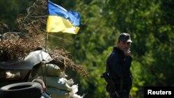 Một binh sỹ Ukraine đứng hút thuốc gần một chốt kiểm soát ở vùng Donetsk.