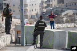 ຕຳຫຼວດຊາຍແດນຂອງ Israel ສັ່ງໃຫ້ຊາຍຜູ້ນຶ່ງຍົກເສື້ອຂອງຕົນຂຶ້ນ ເພື່ອກວດຄົ້ນ ກ່ອນທີ່ຈະອະນຸຍາດ ອອກຈາກ ໝູ່ບ້ານ ອາຣັບ ໃນ Issawiyeh ນະຄອນ Jerusalem, 20 ຕຸລາ, 2015.