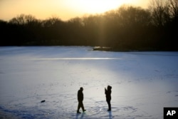 A couple takes photographs on a frozen pond at Franklin Delano Roosevelt Park in Philadelphia, Jan. 3, 2018.