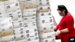 Stacks of ballots await to be counted for the general election inside the Maricopa County Recorder's Office in Phoenix, Nov. 6, 2020.