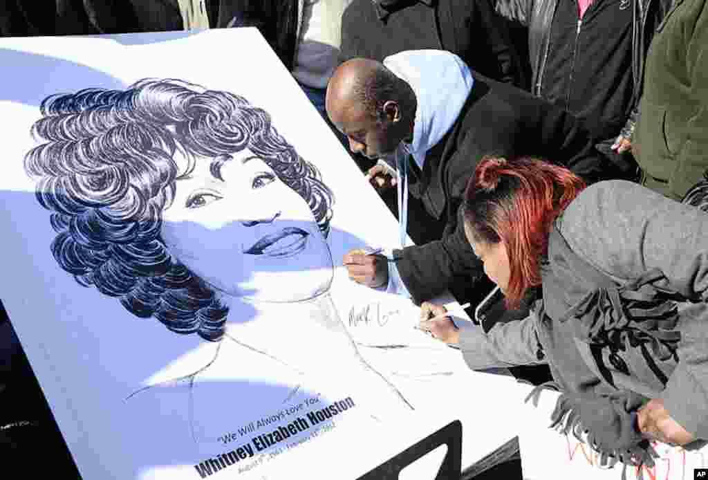 在葬礼举行之际,歌迷们在一个印着惠特尼.休斯顿的肖像的招贴画上签名
