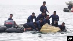 Para penyelam TNI Angkatan Laut menarik bagian dari puing pesawat Sriwijaya Air dari perairan di sekitar Kepulauan Seribu, Minggu (10/1).