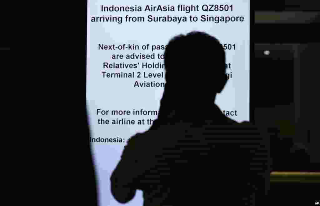 A man is silhouetted against an electronic bulletin board at the Changi International Airport in Singapore, where AirAsia Flight 8501 from Surabaya, Indonesia was scheduled to land, Dec. 28, 2014 .