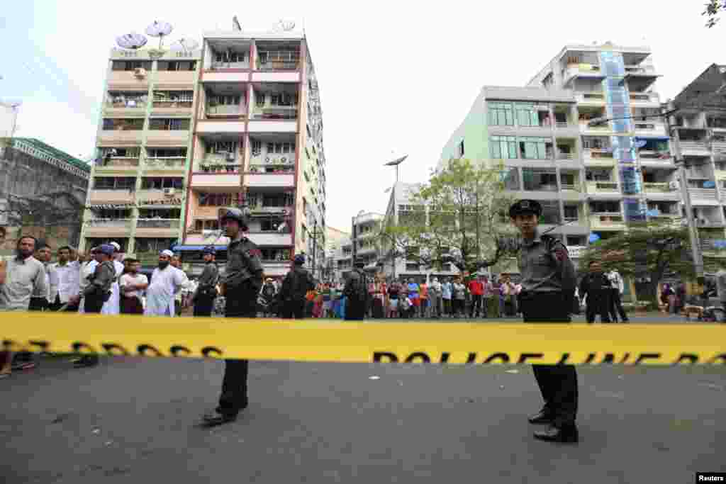 Police stand near a mosque and school dormitory that were damaged by a fire in Rangoon, Burma, April 2, 2013.
