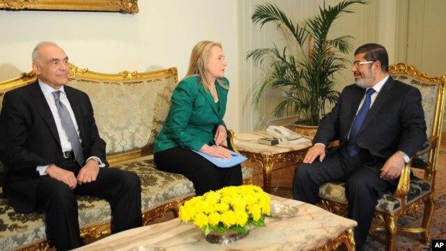 Sekretè Deta Hillary Rodham Clinton (nan mitan) avèk Prezidan ejipsyen an Mohammed Morsi (adwat), epi Minis Afè Etranjè ejipsyen an, Mohammed Kamel Amr nan vil Lekèr (mèkredi 21 novanm 2012).