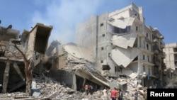 Người dân xem xét một tòa nhà bị hư hại sau các cuộc không kích vào một khu vực của phe nổi dậy ở Aleppo, Syria, 27/8/2016.