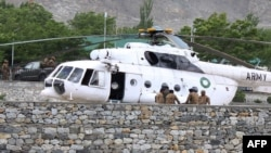 Tentara Pakistan berkumpul di samping sebuah helikopter angkatan bersenjata di rumah sakit militer di mana korban kecelakaan dibawa untuk perawatan di Gilgit (8/5).