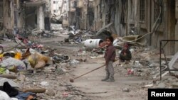 A child clears damage and debris in the besieged area of Homs, Syria, Jan. 26, 2014.