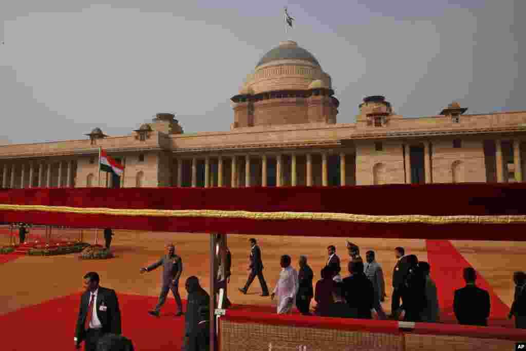 Presiden Sri Lanka Maithripala Sirisena (tengah, berbaju putih) berjalan di karpet merah dengan Presiden India Pranab Mukherjee setelah menginspeksi upacara penerimaan di Istana Presiden di New Delhi (16/2). (AP/Manish Swarup)