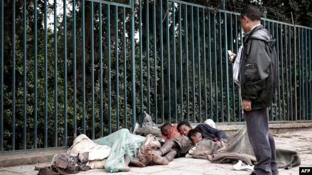 An Ethiopian man uses his mobile phone to take a picture of street children sleeping on a street of Addis Ababa in Ethiopia, (File photo).