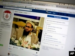 FILE - A photo shows a Facebook site that features one of India's most wanted, Hafiz Saeed, the founder of Lashkar-e-Taiba, a banned organization and a U.S. declared terrorist group, in Islamabad, Pakistan, July 7, 2017.