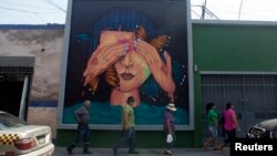 People walk next to a mural at Pachitea street in downtown Lima, March 12, 2015.