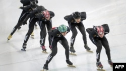 Members of the US speed skating team train wearing their new black suits on the No 2 training rink next to Adler speed skating arena during the Sochi Winter Olympics, Jan. 31, 2014.