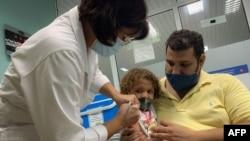 FILE - Pedro Montano holds his daughter Roxana Montano, 3, while she is vaccinated against COVID-19 with a Cuban vaccine, at Juan Manuel Marquez hospital in Havana, August 24, 2021.