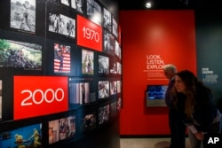 People visit the Pulitzer Prize Photography exhibition at the Newseum, Friday, Dec. 20, 2019, in Washington. (AP Photo/Jacquelyn Martin)