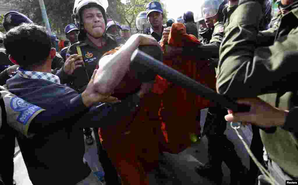 A Buddhist monk shields himself from police officers during a protest in front of the City Hall in central Phnom Penh, Cambodia. About 100 former Boeung Kak lake residents, including Buddhist monks, demanded that the government provide them with more compensation over their forced eviction from the area, to pave way for a private real estate development project, according to protesters.