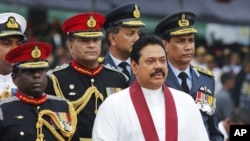 Sri Lanka's President Mahinda Rajapaksa (front) inspects troops from an army vehicle in a parade during a war victory ceremony in Colombo. May 27, 2011.