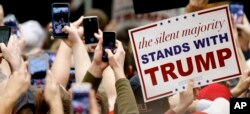 FILE - Supporters of Republican presidential candidate Donald Trump hold up phones and signs at a rally at Radford University in Radford, Virginia, Feb. 29, 2016.